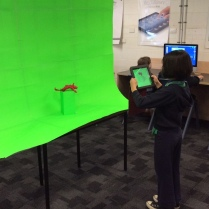 A student creating raw footage with an iPad for a Green screen movie.